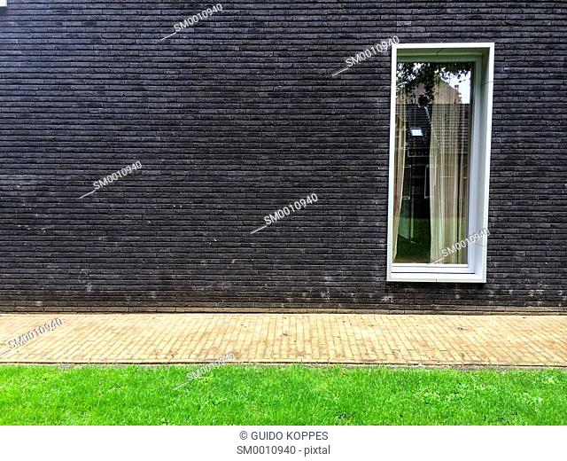 Tilburg, Netherlands. Window in an outside wall of a modern apartment building, situated in a down town park