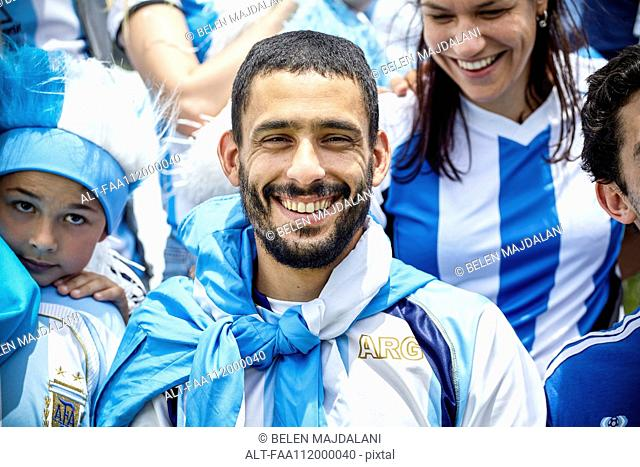 Argentinian football fan smiling at match, portrait