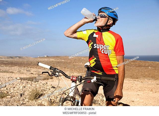 Spain, Canary Islands, Fuerteventura, senior man with mountainbike drinking from bottle