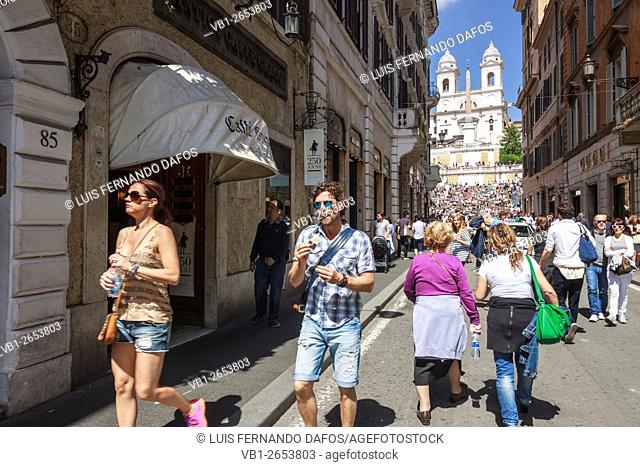Tourists walk past Cafe Greco at Via Condotti with Spanish steps in background. Rome, Italy