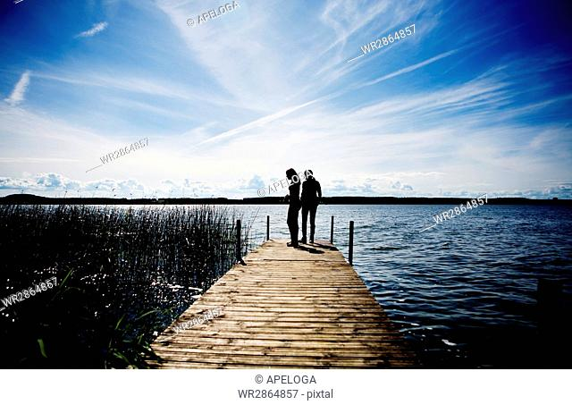 Silhouette mother and daughter standing on pier over lake against sky