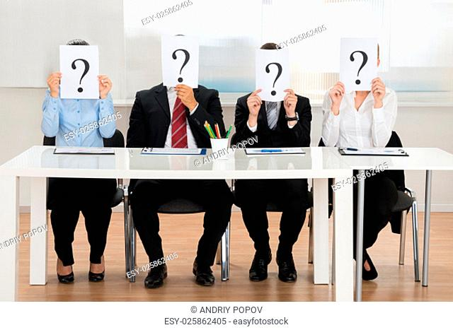 Businesspeople Team Hiding Face With Question Mark Sign At Desk