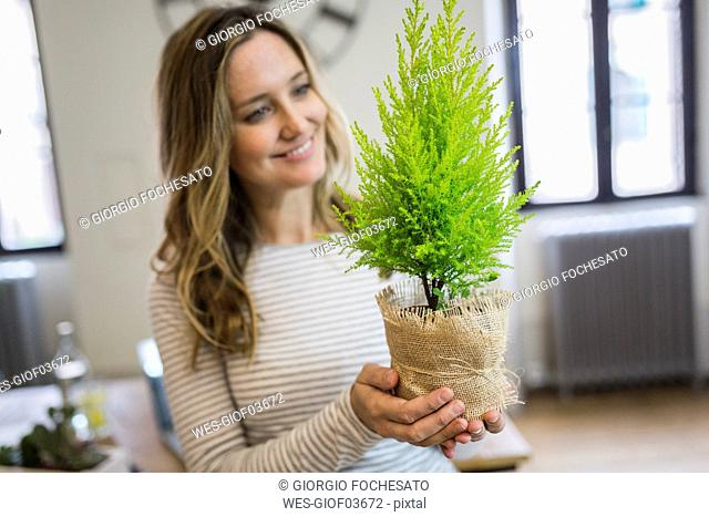 Smiling woman holding plant at home
