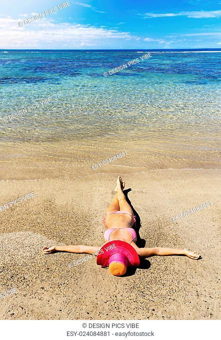 Young fashion woman relaxing on warm tropical beach