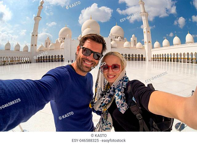 Couple taking selfie in Sheikh Zayed Grand Mosque, Abu Dhabi, United Arab Emirates