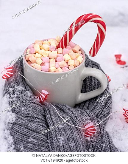 ceramic cup with hot chocolate with marshmallows on white snow wrapped in a gray scarf, next to a glowing Christmas garland