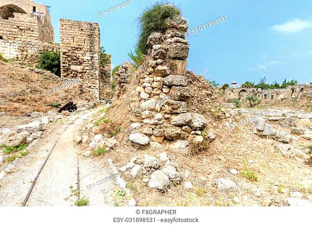 The crusaders' castle in the historic city of Byblos in Lebanon. A view of the exterior and a path, with train tracks, leading to the western part of the...