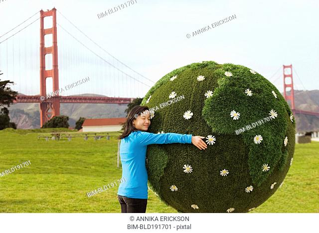 Chinese girl hugging earth topiary