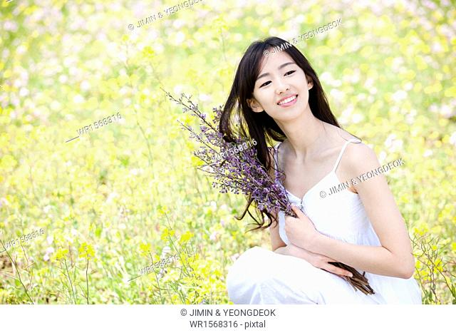 a woman holding a bunch of flowers next to a field