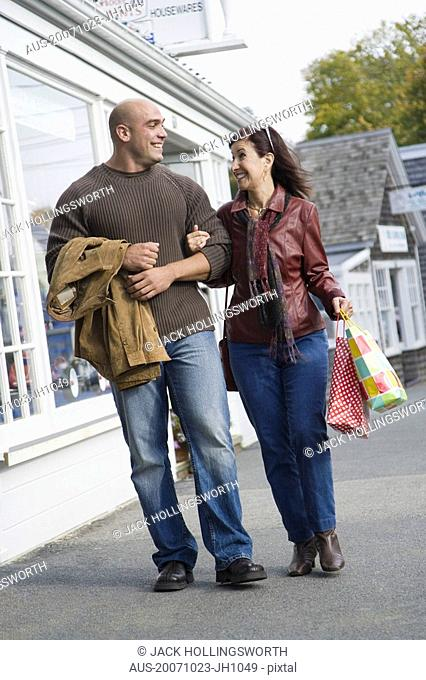 Mature woman and a mid adult man walking with their arm in arm and smiling