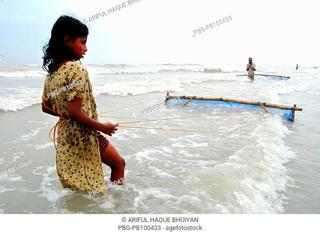 "A girl pulling a fishing net in the waters of the Bay of Bengal, at Kuakata beach in Patuakhali, Bangladesh Kuakata, locally known as ""Sagar Kannya"" or daughter..."