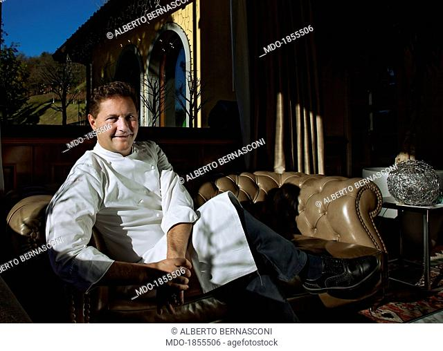 Italian chef Enrico Cerea sitting on a sofa in a photocall shooted at his restaurant awarded with three Michelin stars 'Da Vittorio'