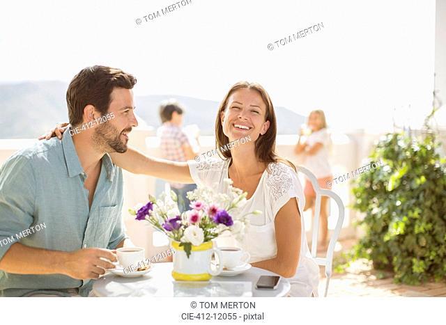 Couple enjoying coffee on balcony