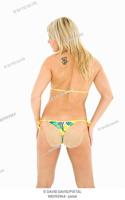Beautiful and sexy caucasian woman in her early 20s posing in a Brazilian thong bikini on a white background