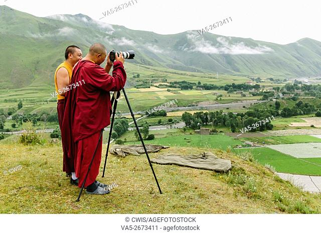 Xinduqiao, Sichuan province, China - The view of two monks playing camera on the mountain top