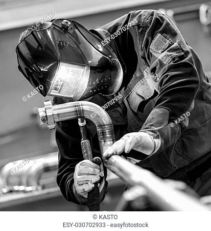 Industrial worker with protective mask welding inox elements in steel structures manufacture workshop. Black and white photo