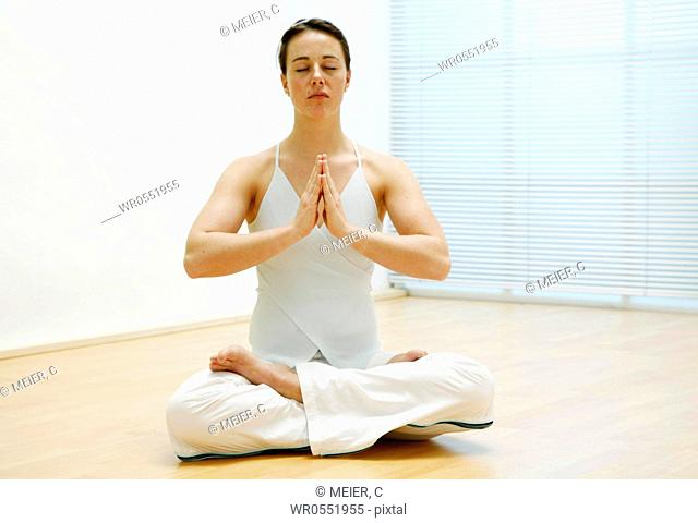 young woman sitting on the floor and is meditating
