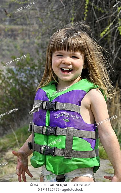 This cute 3 year old Caucasian girl is smiling and happy while playing outdoors She's wearing a green life vest and coverd in mud as she's been playing