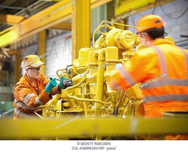 Apprentice engineers at work in factory
