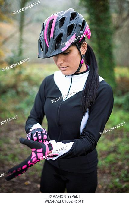 Woman putting on bicycle gloves