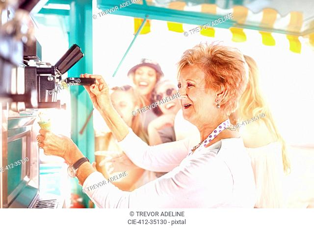 Smiling senior female business owner serving ice cream at food cart