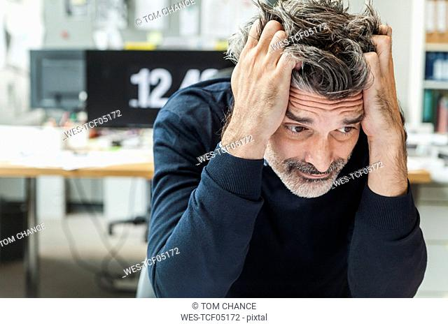Mature man sitting in office with head in hands