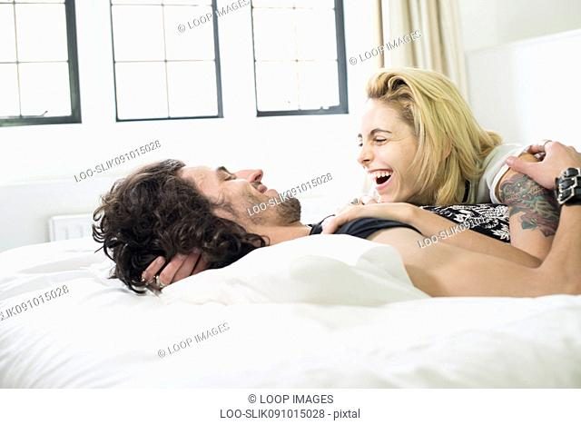 A cool young couple lying on a bed laughing together