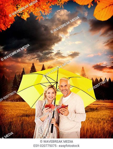Composite image of portrait of happy couple under yellow umbrella