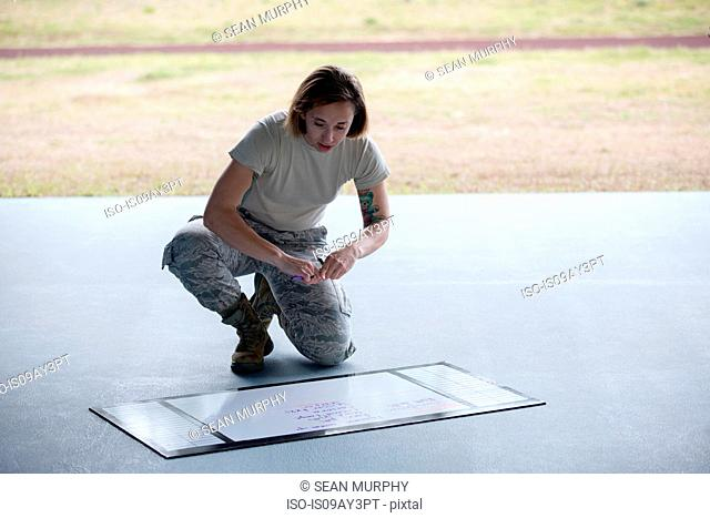 Female soldier preparing training timetable at military air force base