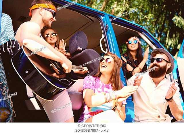 Five young adult friends playing acoustic guitar and clapping by recreational van