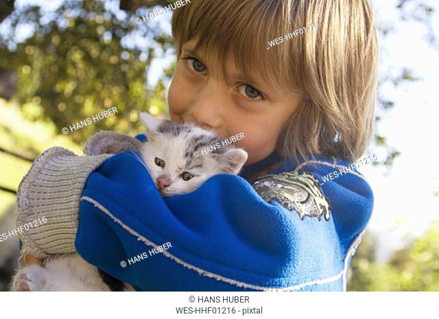 Boy holding kitten, portrait