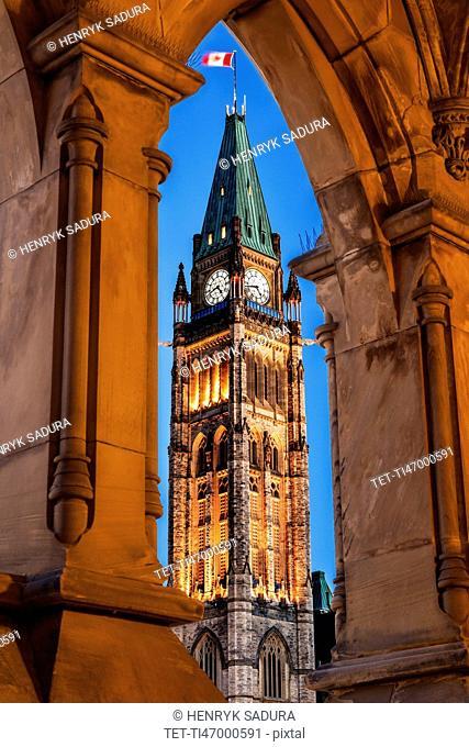 Illuminated Peace Tower seen through lancet arch