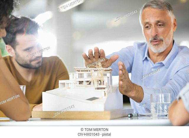 Architects discussing model in meeting