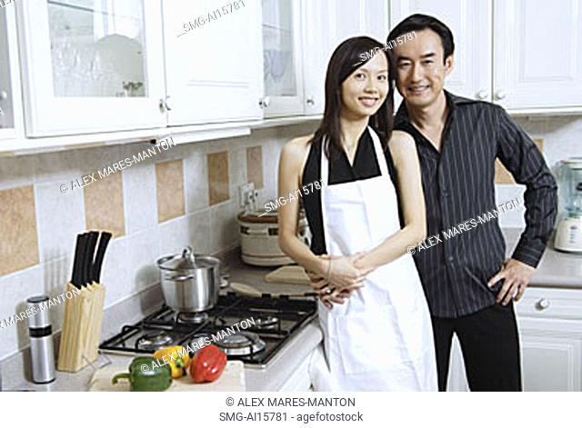 Couple standing in kitchen, smiling at camera