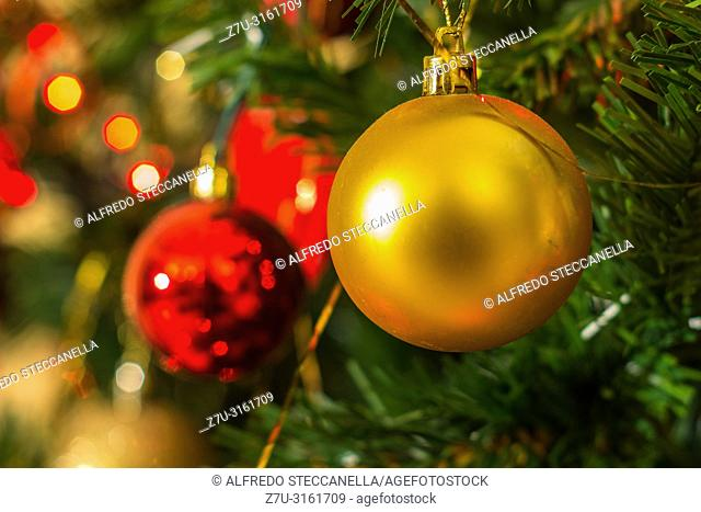 Various Christmas tree decorations and red blurred light on background