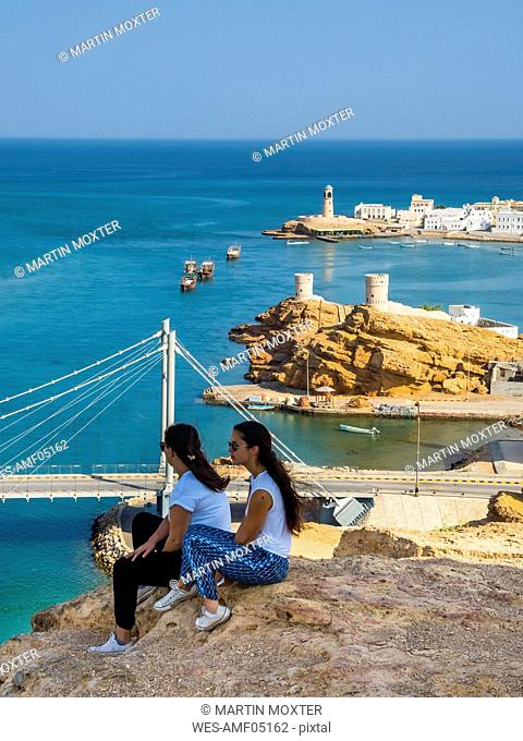 Oman, Ash Sharqiyah, Ad Daffah, back view of two women sitting on a rock in front of seaport Sur