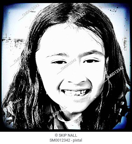A young girl trying to smile when she is wet and cold