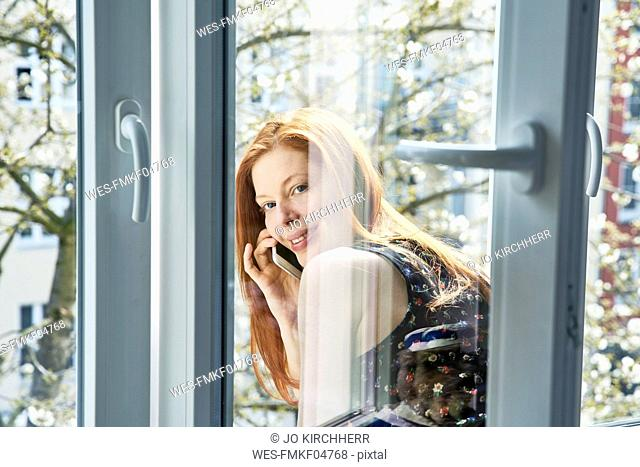 Portrait of redheaded woman on the phone leaning out of window in spring