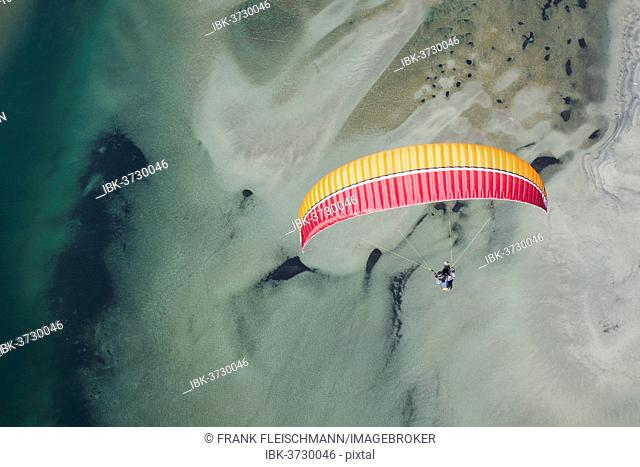 Paraglider over the Maggia river delta with naturally formed water and rocks terrain, Locarno, Kanton Tessin, Switzerland