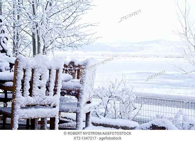 A snowy deck with snow covered table and chairs overlooking a frozen lake in northern colorado