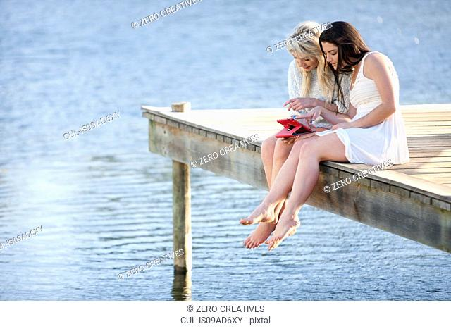 Two young women sitting on pier looking at digital tablet