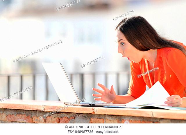 Side view portrait of a surprised entrepreneur working online with laptop in a balcony