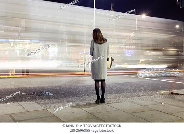 UK,London,South Kensington-Woman waiting to cross busy road at night