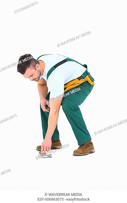Carpenter picking up hammer