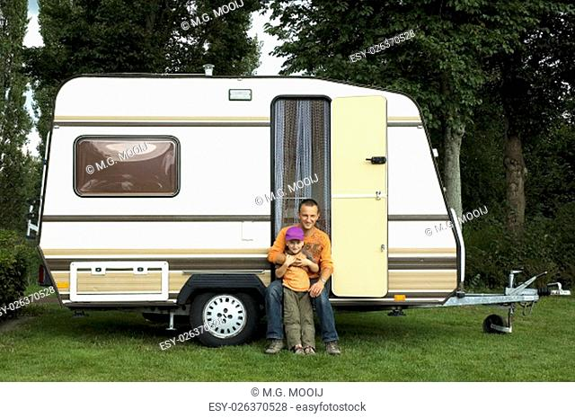 Father and son sitting in front of a caravan