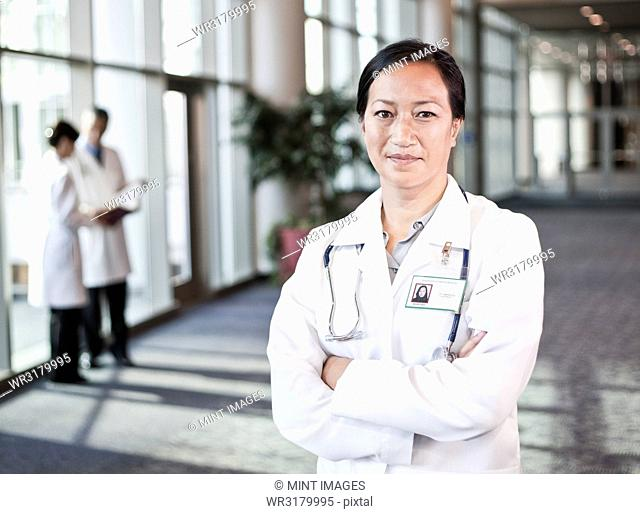 Asian woman doctor in lab coat with stethoscope