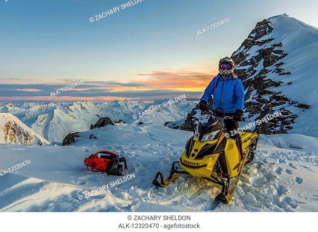 A man straddles a snowmobile on top of Hogsback, in the Chugach Mountains, near Valdez, Southcentral Alaska, USA