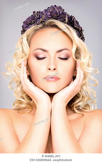 Close-up of gorgeous blond with pure skin and bare shoulders wearing purple headband over grey background