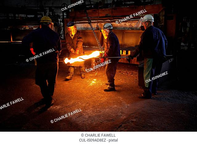 Red hot steel billet which has already been partially pre formed is moved back in to the furnace