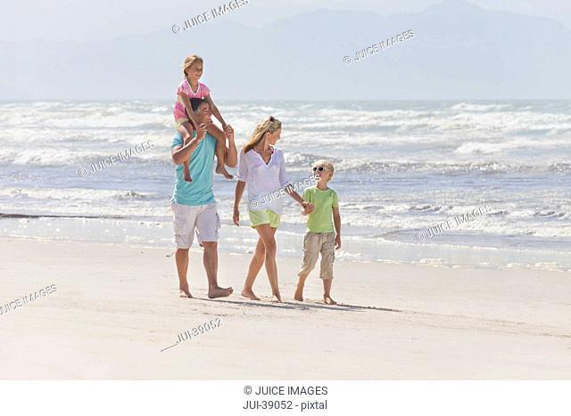 Family walking on sunny beach